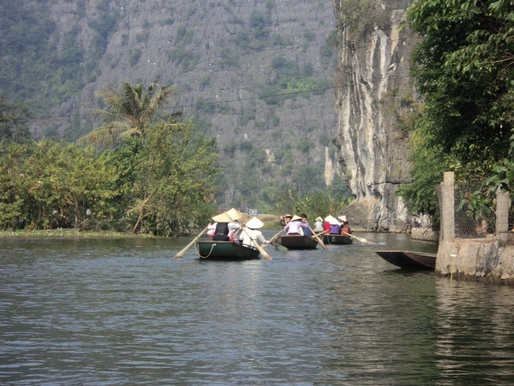 A row of boats entering the famous caves of Ninh Binh